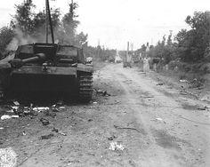 Des Panzern et des véhicules allemands détruits le long de la RN13 à la sortie Nord de Sainte Mère Eglise. Le photographe tourne le dos au village.  Photo prise par Bob Piper (photo collection H.J. Renaud)  Au premier plan un Sturmgeschütz 40 qui a été détruit, le 7 juin 1944, par J. Atchley (il reçu la DSC pour cette action) de la H Co 505th PIR (82nd US AB) avec un 57mm Anti-Tank Gun M1( en arrière-plan à droite) au barrage Nord sur la RN 13.