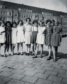 A photo of Anne Frank and her friends who are celebrating Anne's 10th birthday . Anne is pictured second to the left in a dark colored dress.