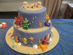 """Beach Babies - Fondant covered 10' and 6"""" round.  Fondant sea creatures with chocolate sea shell and coral.  Dusted with pearl dust. Sand made from graham crackers and cane sugar.  Had planed to have a sand castle on top to give it some height, but ran out of time.  Fun cake to make.  I learned a lot."""