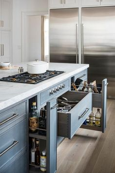 A gray shiplap island painted Benjamin Moore Light Pewter features pot and pan drawers flanked by a pull out spice rack and a pull out utensils rack.