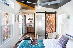 The tiny house is made up of two trailers. One serves as a bedroom, and a porch connects to another trailer. A storage rack built down from the ceiling houses the clients' fishing poles and camping gear. For tiny homes, you must use every square inch of storage!