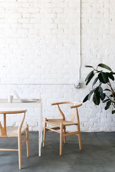 wishbone chairs and concrete floors with white brick wall