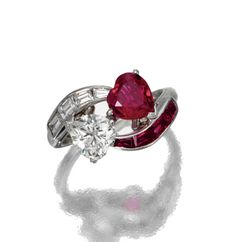 RUBY AND DIAMOND RING, CIRCA 1950.  Of crossover design, set with a heart-shaped ruby weighing approximately 1.10 carats and a heart-shaped diamond weighing approximately .90 carat, flanked by baguette rubies and diamonds, mounted in platinum