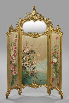 """Large and Opulent Carved Giltwood Boudoir Screen, first quarter 20th century, the painted silk and mirrored glass three-fold screen in the Louis XV taste, the upper portion of the central panel of mirrored glass, the lower portion of polychromed silk in """"Nesting Songbirds"""" decor, the flanking left panel in """"Hollyhocks"""" decor and the right in """"Scarlet and White Geraniums"""" decor, the whole supported on four carved giltwood scroll feet, h. 80-1/2"""", w. 54""""."""