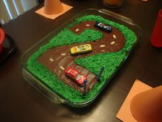 Yellow cake with chocolate frosting. Green frosting swirled with a tooth pick and toy cars placed on top.
