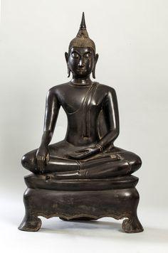 Buddha Maravijaya assis sur un haut socle tripode en virasana touchant la terre à témoin en bumishparshamudra vêtu de la robe monastique utarasanga et coiffé de fines bouclettes surmonté d'un haut rasmi. Bronze à patine brune. Thaïlande. Royaume de U Tong. 15 à 16 ème siècle. Ht 65cm x larg 36 x 19 cm