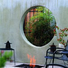 Asian-style elegance  A fire pit underscores a moon window framing a view of giant timber bamboo.