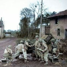 U.S. 607th Tank Destroyer Battalion loading their 3 inch M5 anti-tank gun (pictured top) on a road approaching Metz, France. November 1944.