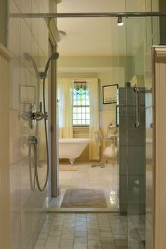 """The main bathroom is actually two bathrooms divided by a walk-through shower. 'Can you guess who got the smaller side?' Tom says. Nancy's side of the bathroom has a claw-foot bathtub with a stained glass window overlooking the backyard.""  Awesome!"