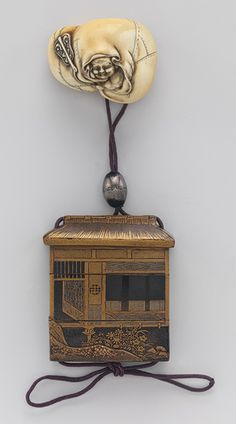 Inrô with design of thatched hut, 18th–19th century Japanese ~  Lacquer; ojime: pewter; netsuke: ivory  Decorated with a combination of lacquer techniques in silver and gold, the inrô in the shape of a thatched hut bears the signature of Koami Shinsaburo. The ivory netsuke, signed by ôhara Mitsuhiro, depicts one of the Seven Gods of Good Luck known as Hotei. A rotund, jolly figure, Hotei's attributes often include a fan and a bag to carry his treasures.