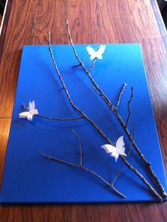 Canvas peint en bleu sur lequel j'ai collé des branches d'arbre et ajouté de jolis papillons.