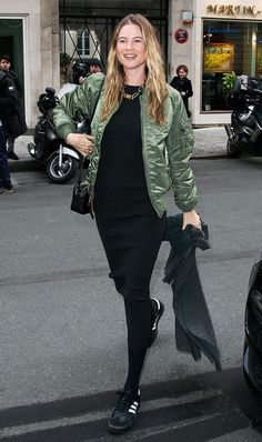 Behati Prinsloo wears a black fitted midi dress, black tights, sneakers, and a green satin bomber jacket.
