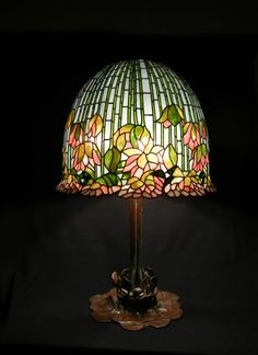 We handcrafted this Flowering Lotus stained glass shade in tranquil tones reminiscent of a Monet watercolor. The exquisite design by Louis Comfort Tiffany is iconic for its flowing shape and its technical difficulty. This table lamp can compliment a variety of interiors, including Traditional, Transitional, Victorian, and Art Nouveau. Or how about as the focal point of a chic white tone-on-tone room?   = medium/tall sized lamp: shade diameter 18; height with base about 27  = Ti...