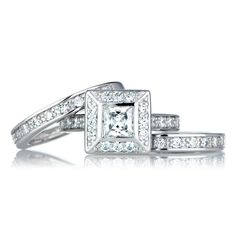 Princess Cut CZ Triple Wedding Ring Set. Find a timeless treasure with 1.21 CT Princess Princess Cut CZ Wedding Ring Set. The silvertone trio features a stunning square art deco designed ring with two half eternity bands. The center stone features a princess cut CZ measuring 1.21-carats and is surrounded with petite round CZ stones. If you're looking to add vintage inspired jewelry to your fingers, then try this ring on for size.