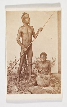 Daniel MARQUIS, Studio portrait of an Aboriginal man standing holding spear, lubra seated on floor