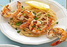 WW Grilled Shrimp Scampi: 1-1/2 lbs fresh or frozen large shrimp,  (20 to 24 shrimp total)  3 tbsp lemon juice 3 cloves garlic, minced 1/4 tsp salt 1/4 tsp freshly ground black pepper (4 oz) dried vermicelli pasta or  whole-wheat vermicelli pasta  2 tbsp snipped fresh Italian (flat-leaf) parsley Lemon wedges 1 tbsp olive oil 4 (10 inch) wooden skewers Note: (Soak skewers in water for at least 30 minutes; drain before using).