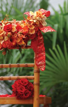 Beautiful garland of fresh flowers including cymbidium orchids, miniature calla lilies, roses, montbreetia, gloriosa lily and celosia with Oriental-inspired ribbon all accenting a chivari chair for a Thai wedding created by celebrity event designer Scot Wedgeworth.  www.scotwedgeworth.com
