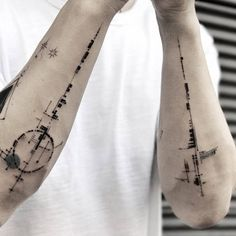 Matching abstract tattoos on both forearms.