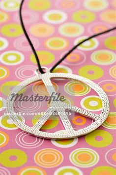 Stock photo of Peace Sign Necklace on retro-inspired background. Premium Royalty-Free, 600-03601395 © Jean-Christophe Riou / Masterfile. All rights reserved.