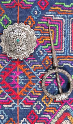 Bhutanese woven fabric and silver shoulder pins.