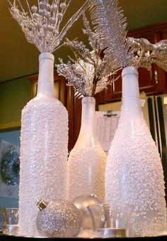 Get a few different shaped wine bottles and a tall magnum bottle, add white spray paint (or silver), roll the bottles in Epsom Salt (yes) or use glitter and arrange on a tray with some candles. Sounds pretty easy