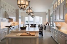 dodson-interiors-whitekitchen.  The traditional cabinets, marble countertops and stone floor make this classically styled kitchen feel so clean and open. The furniture color, the lights in the upper cabinets keep this kitchen from feeling stark.