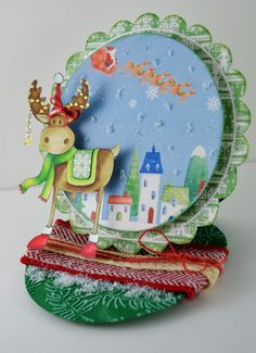 Gini Williams Cagle designing for @CraftersCompUS  Circle Easel Card -  Nordic Christmas EZMount Stamp Set - Christmas Cheer Nordic Christmas Papercrafting CD-ROM Spectrum Noir Markers :BT1, EB1,EB2, EB3, EB4, EB6, JG2, LG2, LG4, LG5, DR1, DR3, DR7 Collall Tacky Glue May Arts Ribbon Flower Soft Ultra Fine White