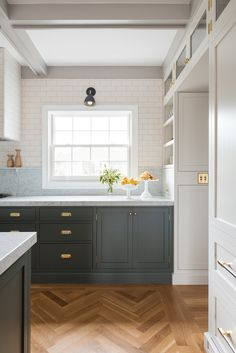 Kitchen flush mount doors grey lower cabinetry white upper cabinets wrap around marble countertop white subway tile wall backsplash custom open shelving moldings panelled walls herringbone hardwood floor natural oak border frames.