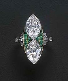 A BELLE EPOQUE DIAMOND AND EMERALD RING   The two marquise-cut diamonds set vertically with calibré-cut emeralds between, to the diamond trefoil shoulders and plain hoop, mounted in platinum and gold, circa 1915, with French assay mark for gold, no. 0439 to the hoop, with blue case by Boucheron