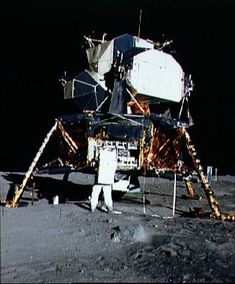 """Lunar Module """"Eagle"""" on the Moon. Aldrin is opening the stowage area and preparing to unload the scientific experiments package. Beyond the right leg is the solar wind experiment, and beyond that the lunar surface TV camera. (NASA photo ID AS11-40-5927"""
