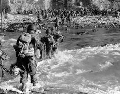 U.S. reinforcements wade through the surf as they land at Normandy in the days following the Allies' June 1944, D-Day invasion of occupied France. (AP)