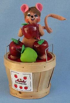 """Annalee Doll Description: Open eyes, open mouth, brown body, brown hair, red bandana print neckerchief, holds red apple, in """"Annalee Orchards"""" wooden bushel basket with red and green apples. Companions are 350913 and 350413."""