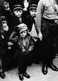 AMERICA IS DOING THE SAME WITH OUR YOUTH (not quite this young militarily) Little girl in the Hitler Youth.