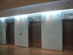 KPMG: Revestimiento del hall - Cristal templado de 6 mm., incoloro con cara posterior pintada, aplicado sobre pared como revistimiento con junta abierta.
