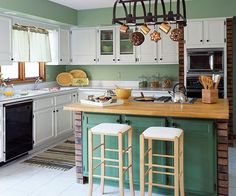 Creamy white paint on formerly dark cabinets can make a kitchen feel larger; such was the case for this kitchen. To add a dose of color, paint your island a bright hue. This island was painted a darker shade of green than the walls to help it stand out. Faux wrought-iron knobs tie in the updated cabinets with the black light fixture/pot rack.