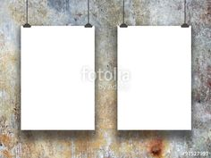 Two hanged blank paper sheet frames with clips on blue and brown concrete wall background