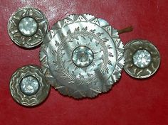 ca 18th century set of carved mother of pearl buttons with paste stone in center, the set consisting of one large button with large metal loop shank and three small stud buttons, the stud also being carved from shell. Probably French