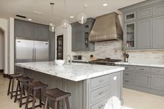 Stunning L-shaped kitchen with gray ceiling height cabinets flanking the stainless steel stove, ...