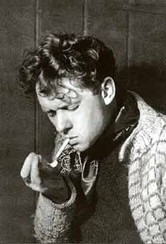 """Dylan Thomas (1914-1953) was a Welsh poet and writer, whose public readings, particularly in America, won him great acclaim; his sonorous voice with a subtle Welsh lilt became almost as famous as his works. His best-known works include the """"play for voices"""" Under Milk Wood and the celebrated villanelle for his dying father, """"Do not go gentle into that good night""""."""