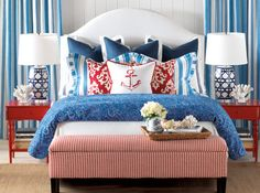 Blue and white bedding wiith red accent pillows. Coastal Living