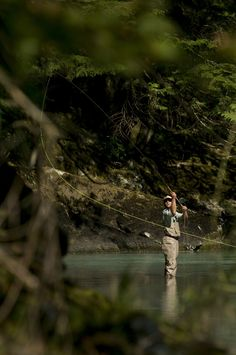 A man casts in a river wearing waders while fly fishing in Squamish, British Columbia.