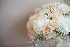 Soft peach and white bridal bouquet with baby's breath, roses, carnations and anemones.