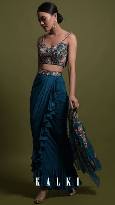 #TealWatersSeries Painstaking autumn sequins and hand-done French-knots on luxe silks in an opulent hue in deep water renders this fiesta slit skirt style as extraordinary and almost magical design for an evening Mehendi ceremony. Consisting of a side-slit skirt, multi-embroidered bustier, a sheer sleeve-cut jacket and a gamut of eclectic hue makes it worthy of a funky Mehendi ceremony!  KALKI Expert Tip: French braided updo with fresh flowers and a winged eyeliner to keep the drama going Designer Party Wear Dresses, Indian Designer Outfits, Indian Outfits, Party Dresses, Draped Skirt, Slit Skirt, Drape Skirt Pattern, Indian Dress Up, Simple Lehenga
