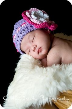 Sleeping newborn baby girl, snuggled in a bowl, wearing a beautiful knit hat.  Natural window light.
