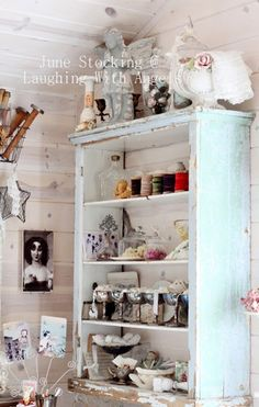 This is a gorgeous shabby chic craft room by June Stocking from Laughing With Angels blog. Her home and blog are absolutely stunning and her story is so heart warming! I love the old chippy vintage shelf unit in this craft space and all the shabby notions on the shelves!