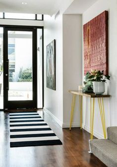 Geometric design adds depth to this modern and simplistic entryway. By combining unique furniture and colorful accessories, your space is sure to reflect your personal style as well.