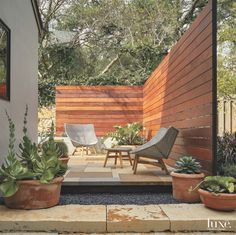 In the back of the house, landscape designer Bill Roberts of 3 Phase Design Studio created an outdoor living area marked by an ipe wood wall. A pair of chairs and a footstool from Dedon's Mbrace collection sit atop tricolored limestone paving. Outdoor Seating Areas, Outdoor Living Areas, Outdoor Rooms, Outdoor Walls, Outdoor Decor, Backyard Seating, Outdoor Patios, Outdoor Kitchens, Outdoor Projects