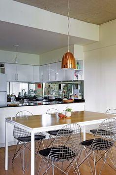 Cocina comedor integrados en un monoambiente con buenas ideas de sectorización. La lámpara de cobre pone el acento sobre la mesa del comedor.