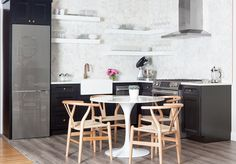 Small black and white kitchen features black cabinets adorned with aged brass knobs paired with white quartz countertops, Silestone Bianco Orion, and a white marble hexagon tile backsplash, placed next to a Bosch 800 Series Refrigerator.