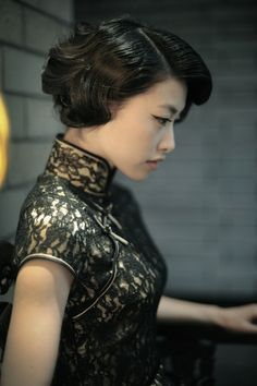 Cheongsam. The look might be later than 20s? Regardless, great hair!